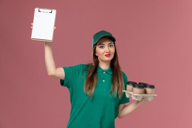 Corriere femminile di vista frontale in uniforme verde e mantello che tiene il blocco note e le tazze di caffè di consegna sul lavoratore di lavoro di consegna uniforme di servizio della parete rosa chiaro