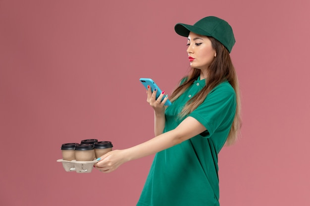 Front view female courier in green uniform and cape taking photo of delivery coffee cups on pink wall service uniform delivery job lady