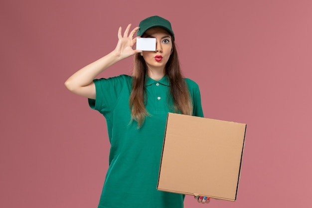 Front view female courier in green uniform holding food delivery box and card on the pink wall company service uniform delivery work job