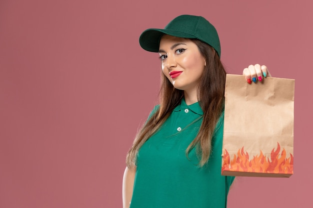 Front view female courier in green uniform holding paper food package on the pink wall job service uniform delivery worker
