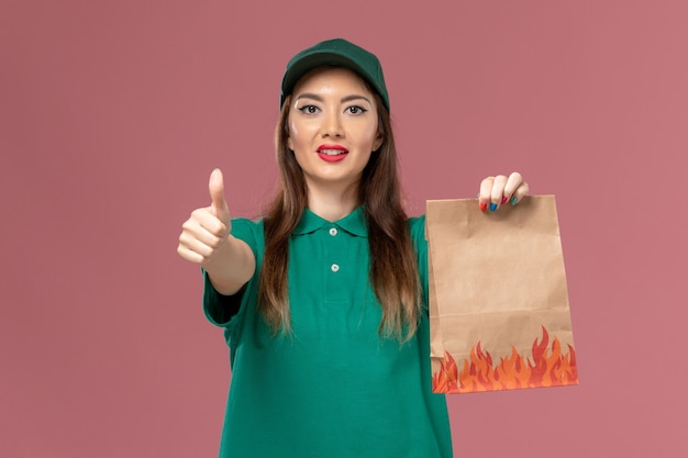 Front view female courier in green uniform holding paper food package on pink wall service uniform delivery job