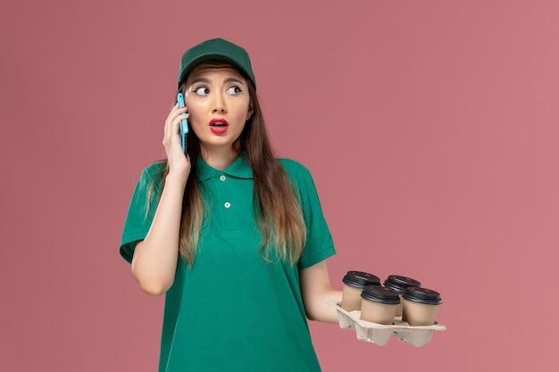 Corriere femminile di vista frontale in uniforme verde parlando al telefono e tenendo le tazze di caffè di consegna sul lavoro di consegna uniforme di servizio parete rosa chiaro