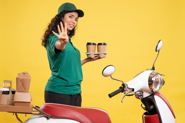Front view female courier in green uniform with coffee on a yellow background color job delivery work food woman service worker