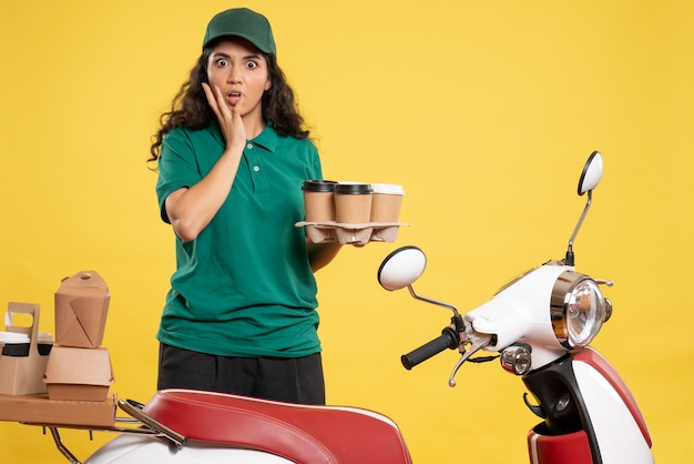 Front view female courier in green uniform with coffee on a yellow background color service worker job delivery work food woman