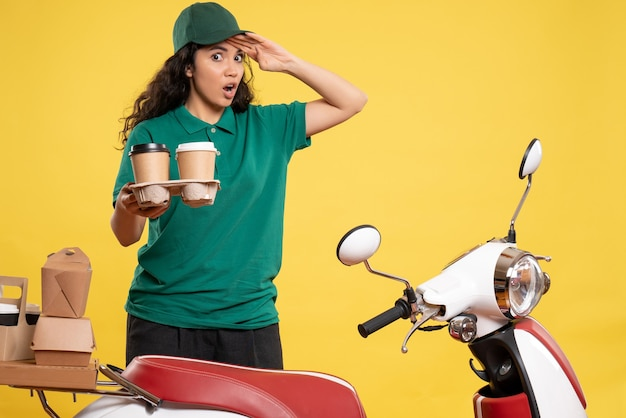 Front view female courier in green uniform with coffee on the yellow background service worker job delivery work food woman color