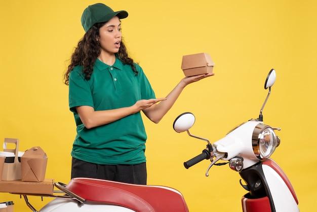 Vista frontale corriere femminile in uniforme verde con un piccolo pacchetto di cibo sullo sfondo giallo lavoro colore lavoro consegna lavoro donna addetta al servizio