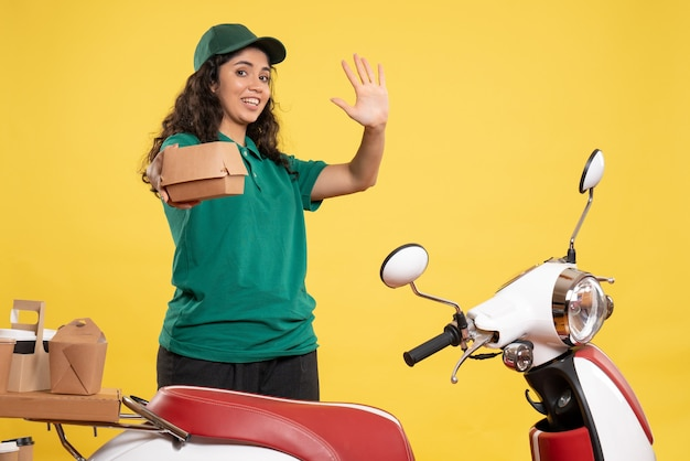 Corriere femminile vista frontale in uniforme verde con un piccolo pacchetto di cibo su sfondo giallo lavoro colore lavoro donna addetta alla consegna cibo