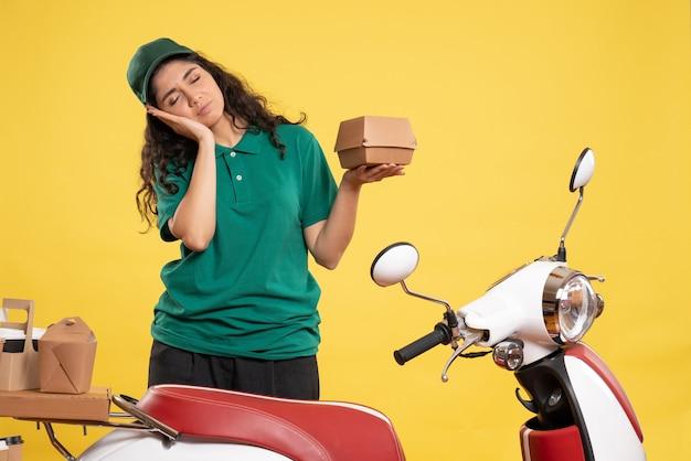 Corriere femminile vista frontale in uniforme verde con un piccolo pacchetto di cibo su sfondo giallo colori del lavoro consegna del lavoro cibo donna addetta al servizio