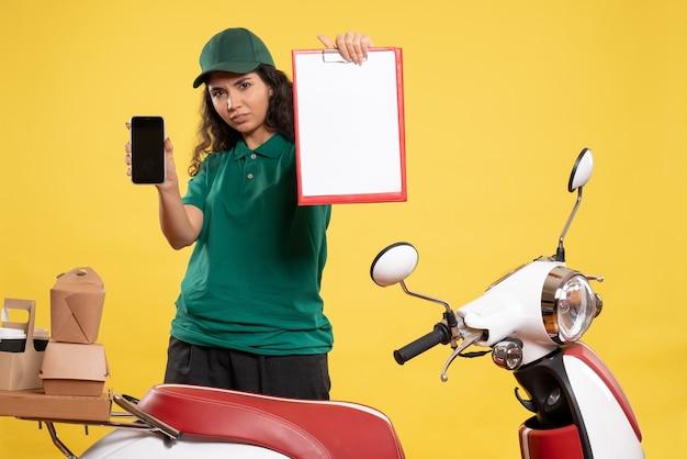 Corriere femminile vista frontale in uniforme verde con telefono e nota di file sullo sfondo giallo lavoratore di servizio consegna lavoro lavoro cibo