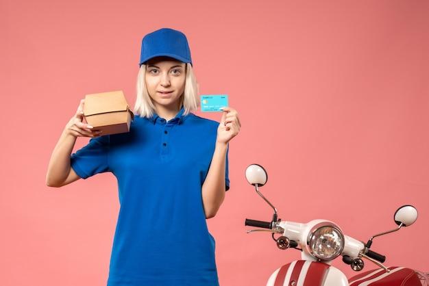 Женский курьер, вид спереди, держащий банковскую карту и небольшой пакет с едой на розовом