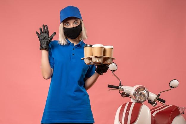 ピンクのコーヒーカップを保持している正面図の女性宅配便