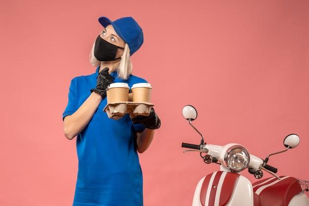 Вид спереди женский курьер, держащий кофейные чашки на розовом