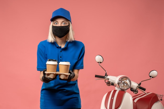 Front view female courier holding coffee cups on pink