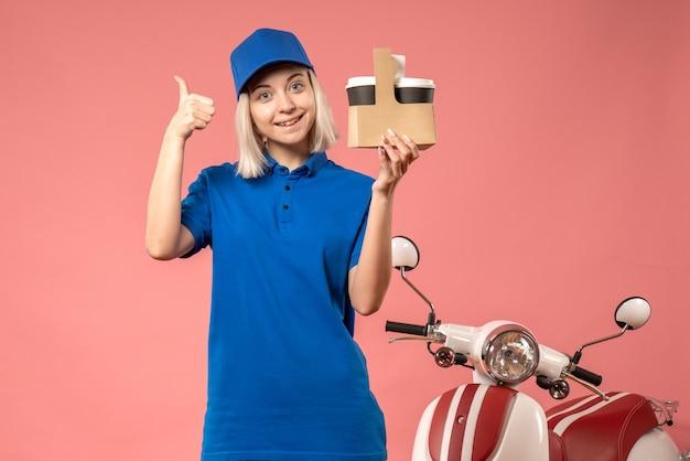 Corriere femminile di vista frontale che tiene le tazze di caffè sul rosa
