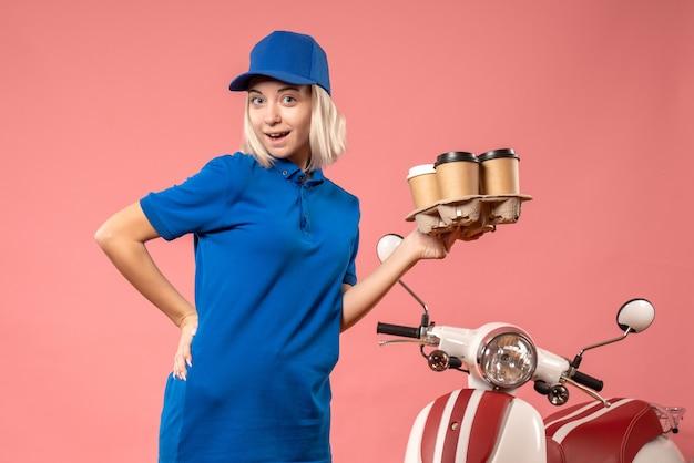 ピンクの配達コーヒーを保持している正面図の女性の宅配便