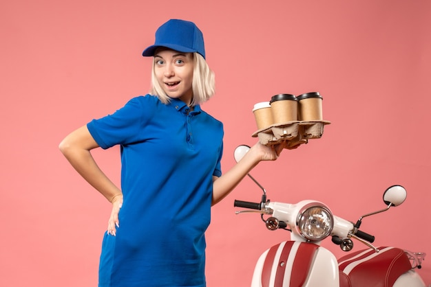 Front view female courier holding delivery coffee on pink