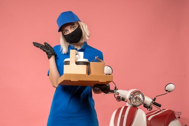 ピンクのフードボックスを保持している正面図の女性の宅配便