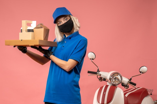 Front view female courier holding food boxes on a pink
