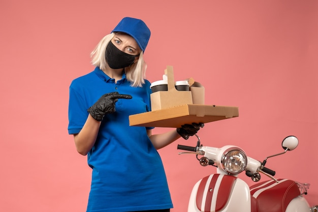 Front view female courier holding food boxes on pink
