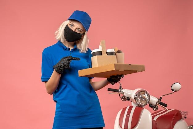 Corriere femminile di vista frontale che tiene le scatole dell'alimento sulla rosa