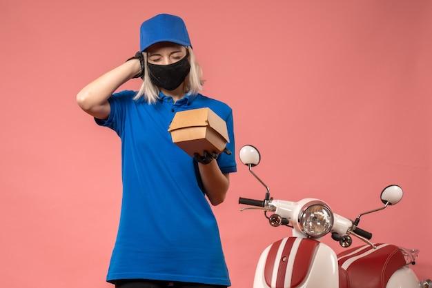 Вид спереди женщина-курьер, держащая маленький пакет с едой на розовом столе, униформа работника службы доставки, вирус covid- job