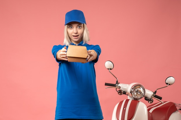 Front view female courier holding little food package on a pink