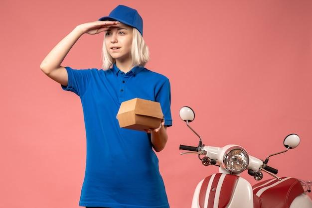 Corriere femminile di vista frontale che tiene piccolo pacchetto di cibo sul rosa