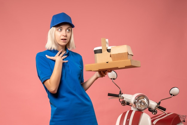 ピンクのピザボックスとコーヒーを保持している正面図の女性の宅配便