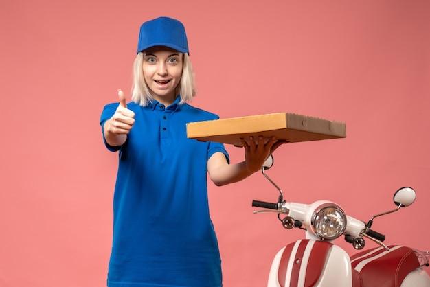 ピンクのピザボックスを保持している正面図の女性の宅配便