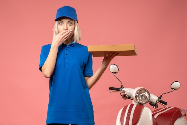 Front view female courier holding pizza box on a pink