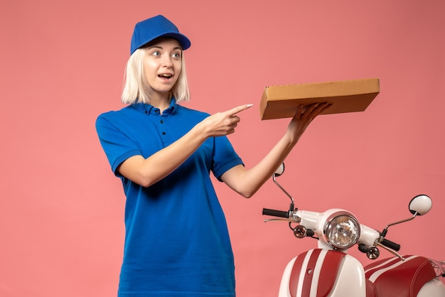 Front view female courier holding pizza box on pink