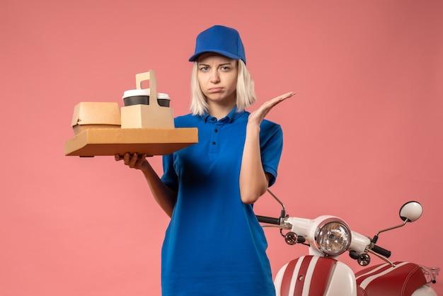 Corriere femminile di vista frontale che tiene la scatola della pizza sul rosa