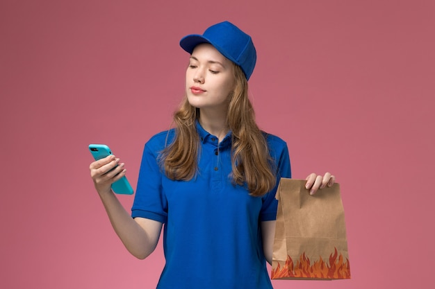 Вид спереди женщина-курьер в синем, держащая телефон и продуктовый пакет на розовом светлом столе, служба униформы, работа компании