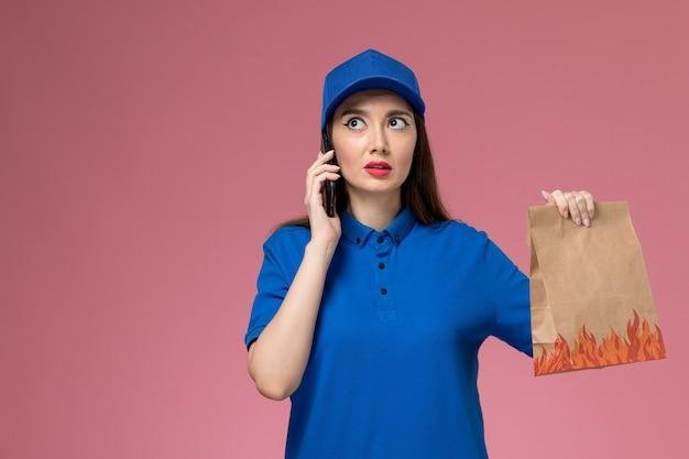 ピンクの壁に電話と食品パッケージを保持している青い制服と岬の正面図の女性の宅配便