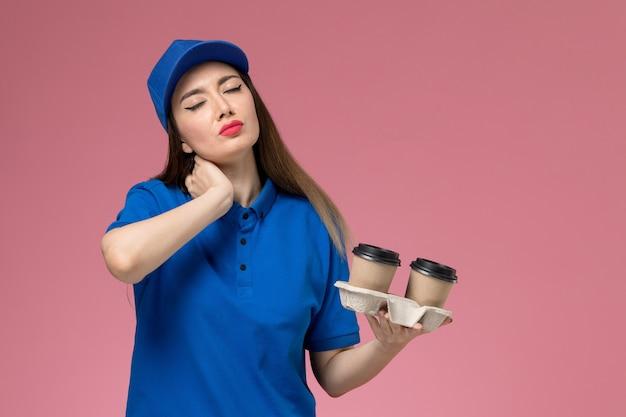 Женский курьер в синей униформе и плаще, держащий коричневые кофейные чашки, с болью в шее на розовой стене, вид спереди