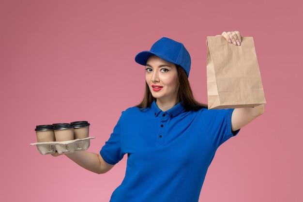 Женский курьер в синей униформе и плаще, держащий кофейные чашки на розовой стене, вид спереди