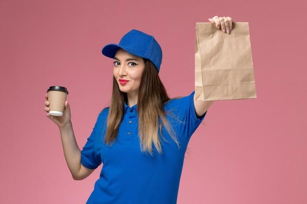 ピンクの壁に配達コーヒーカップ食品パッケージを保持している青い制服と岬の正面図女性宅配便