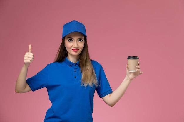 Женщина-курьер в синей форме и плаще, держащая чашку кофе на розовой стене, вид спереди