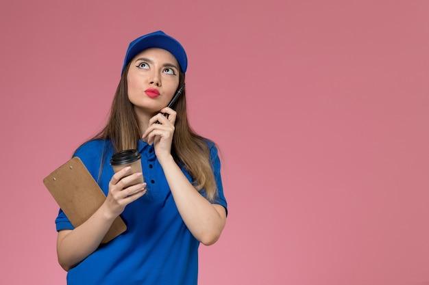 淡いピンクの壁に考えて配達コーヒーカップを保持している青い制服と岬の正面図女性宅配便