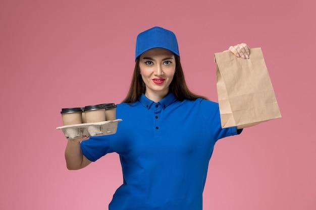 淡いピンクの壁に配達コーヒーカップと食品パッケージを保持している青い制服と岬の正面図女性宅配便