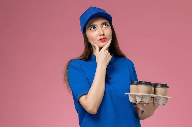 青い制服を着た正面図の女性の宅配便と配達のコーヒーカップを保持し、ピンクの壁で考える岬