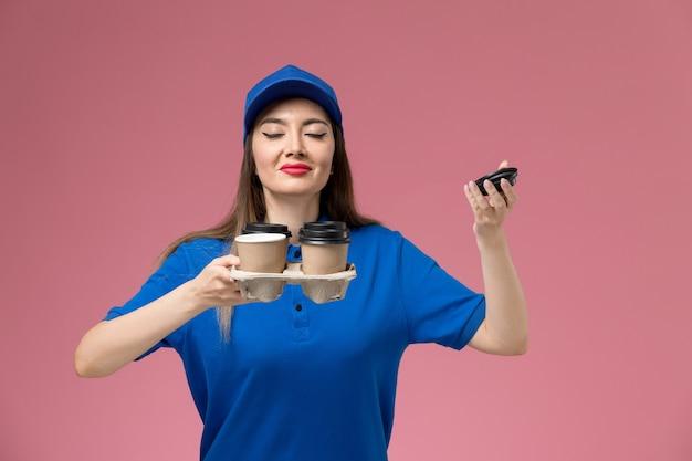 青い制服を着た正面図の女性の宅配便とピンクの壁に香りの香りの配達コーヒーカップを保持している岬