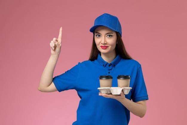 ピンクの壁に上げられた指で配達コーヒーカップを保持している青い制服と岬の正面図の女性の宅配便