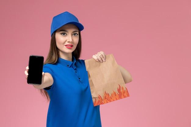 ピンクの壁に彼女の電話と紙の食品パッケージを保持している青い制服と岬の正面図の女性の宅配便