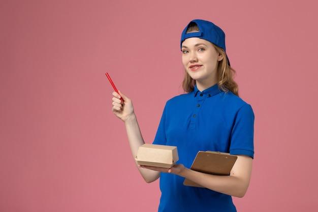 青い制服とケープの正面図の女性の宅配便は、小さな配達食品パッケージのメモ帳を保持し、ピンクの壁に書いています、求人サービスの従業員