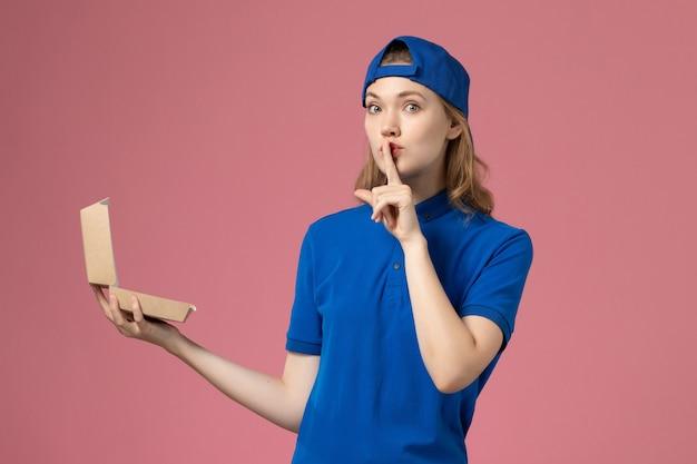 淡いピンクの壁に小さな配達食品パッケージを保持している青い制服と岬の正面図の女性の宅配便、配達制服サービス従業員の女の子