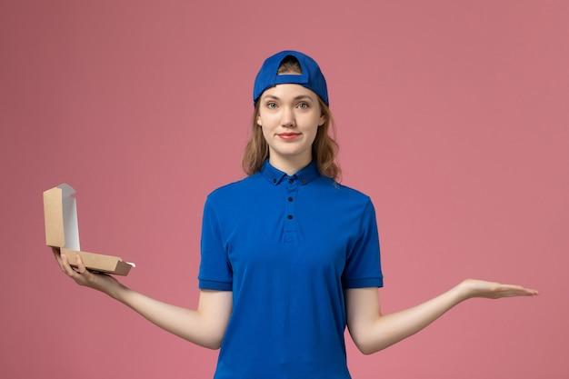 淡いピンクの壁に小さな配達食品パッケージを保持している青い制服と岬の正面図の女性の宅配便、配達制服サービスの従業員の仕事