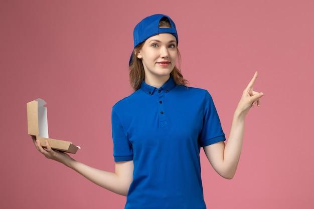淡いピンクの壁に小さな配達食品パッケージを保持している青い制服と岬の正面図女性宅配便、配達制服サービス従業員労働者