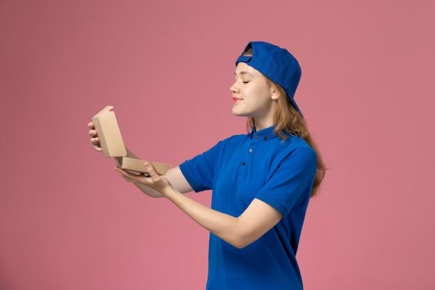 淡いピンクの壁に小さな配達食品パッケージを保持している青い制服と岬の正面図の女性の宅配便、配達制服サービスの仕事の従業員