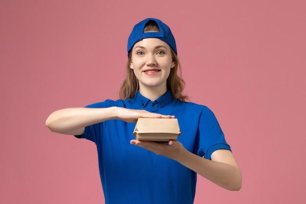 淡いピンクの壁に小さな配達食品パッケージを保持している青い制服と岬の正面図の女性の宅配便、配達制服サービスワーカーの従業員